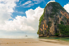 Belle nuvole, alta scogliera e un piccolo yacht nel mare Fotografia Stock