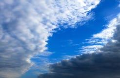 Belle nuvole bianche e scure, pioggia, cumuli contro un cielo blu Nuvole pittoresche e fantastiche Paesaggio normale immagine stock libera da diritti