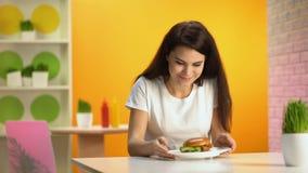 Belle odeur appréciante femelle d'hamburger savoureux et du sourire sur la caméra, appétit clips vidéos