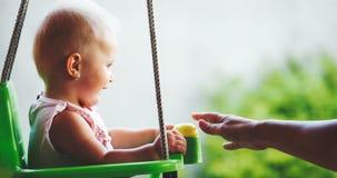 Belle oscillation de bébé extérieure avec soin faimly Images stock