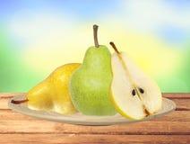 Belle pere verdi e gialle fresche sul piatto sulla tavola sopra Na Fotografia Stock