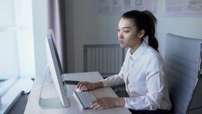 Belle personne féminine asiatique travaillant devant le moniteur dans le bureau clips vidéos