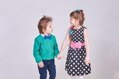 Belle petit garçon et fille, mains de prise et regard à l'un l'autre Images stock