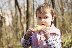 Belle petite fille appréciant une pizza délicieuse en nourriture de nature image libre de droits