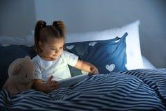 Belle petite fille avec l'instrument et le jouet dans le lit la nuit photographie stock libre de droits