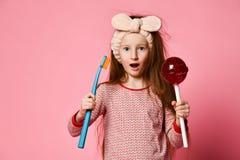 Belle petite fille avec la brosse à dents et les lolipops doux photo libre de droits