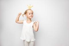Belle petite fille avec la couronne de papier posant sur le fond blanc à la maison Photo libre de droits