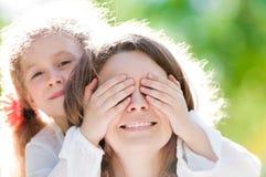 Belle petite fille avec la main sur des yeux de mère Image libre de droits