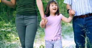 Belle petite fille avec syndrome de Down marchant avec des parents Photos stock