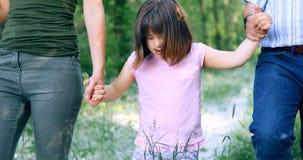Belle petite fille avec syndrome de Down marchant avec des parents Photo stock