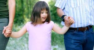 Belle petite fille avec syndrome de Down marchant avec des parents Images stock