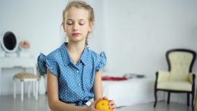 Belle petite fille avec une orange dans des ses mains clips vidéos