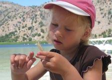 Belle petite fille blonde dans un chapeau rose observant une oreille de blé image stock