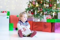 Belle petite fille d'enfant en bas âge lisant un livre sous l'arbre de Noël Photos stock