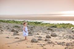 Belle petite fille d'enfant en bas âge observant le coucher du soleil Image libre de droits