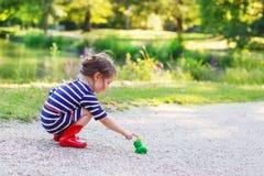 Belle petite fille dans des bottes de pluie rouges jouant avec la grenouille en caoutchouc images stock