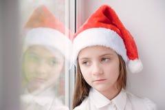 Belle petite fille dans le chapeau de Santa près de la fenêtre Images libres de droits