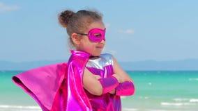 Belle petite fille dans le costume de super h?ros, habill? dans un manteau rouge et le masque du h?ros Jeux sur le fond banque de vidéos