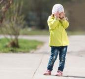 Belle petite fille dans le visage de dissimulation de manteau jaune avec des mains Photos stock