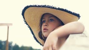 Belle petite fille dans un chapeau se reposant sur les escaliers menant à la mer et aux regards dans la distance photo libre de droits