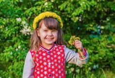 Belle petite fille dans une guirlande des pissenlits Photographie stock libre de droits