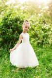 Belle petite fille dans une robe blanche posant dans l'herbe Photos stock