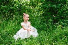 Belle petite fille dans une robe blanche posant dans l'herbe Photographie stock libre de droits