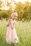 Belle petite fille dans une robe blanche posant dans l'herbe Photo libre de droits
