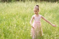 Belle petite fille dans une robe blanche posant dans l'herbe Image libre de droits