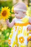 Belle petite fille dans une robe jaune sentant un tournesol Image libre de droits