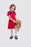 Belle petite fille de sourire dans une robe rouge avec un ours de jouet Photos stock