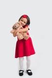 Belle petite fille de sourire dans une robe rouge avec un ours de jouet Photos libres de droits