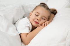 Belle petite fille dormant dans le bâti bedtime photos stock