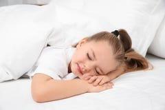 Belle petite fille dormant dans le bâti bedtime photo stock