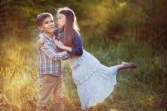 Belle petite fille embrassant un garçon en parc Photographie stock