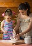 Belle petite fille faisant cuire avec sa mère Photos stock