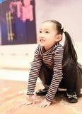 Belle petite fille gaie jouant l'au sol de plaisir sur le terrain de jeu Photos stock