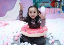 Belle petite fille gaie jouant l'au sol de plaisir sur le terrain de jeu Image libre de droits