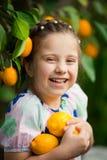Belle petite fille heureuse dans la robe colorée dans le jardin Lemonarium de citron sélectionnant les citrons mûrs frais dans so Photo stock