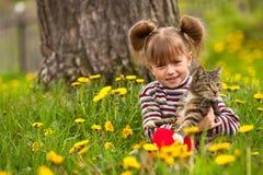 Belle petite fille jouant avec un chat Image libre de droits