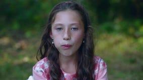 Belle petite fille mangeant une banane dans le jardin banque de vidéos