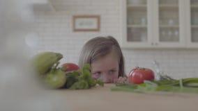 Belle petite fille regardant la table avec des tomates, cucchini, verts, oignon Enfant prenant une tomate et une course banque de vidéos