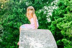Belle petite fille s'asseyant sur la structure en pierre photo libre de droits