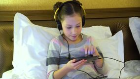 Belle petite fille s'asseyant sur le lit dans l'hôtel dans des écouteurs et jouant un jeu sur un smartphone banque de vidéos