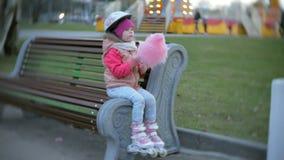 Belle petite fille s'asseyant sur un banc en parc d'attractions, mangeant le roulement doux rose de sucrerie de coton sur des pat banque de vidéos