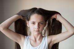 Belle petite fille se soulevant vers le haut de ses cheveux à la main Photographie stock