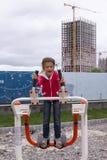 Belle petite fille sur le vieux simulateur en métal autour de la cour de jeu en stationnement image stock