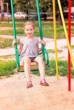 Belle petite fille sur oscillations extérieures dans le terrain de jeu Images stock