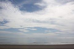 Belle photo de plage de sable et de mer bleue sous le ciel nuageux photographie stock