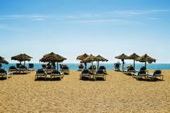 Belle plage avec des lits pliants et des parapluies photo stock